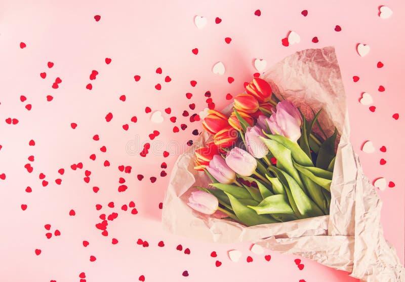 在软的粉红彩笔背景的春天美丽的郁金香花与红心闪亮金属片 Mother& x27;s天,欢乐的贺卡 库存图片