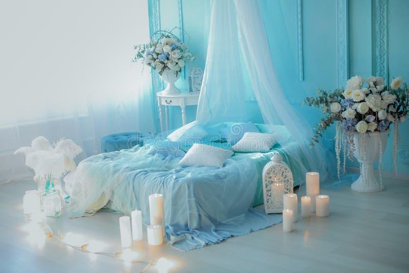 在软的蓝色口气的卧室装饰与蜡烛 免版税库存照片