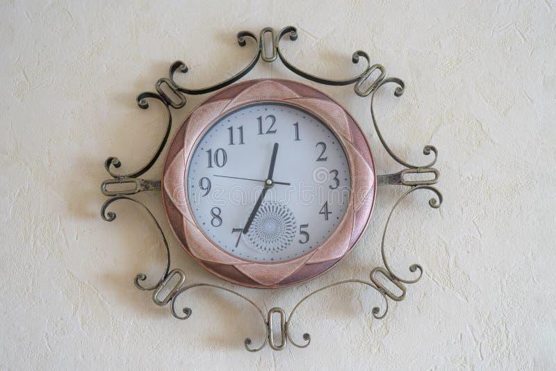 在轻的背景墙纸的壁钟 库存照片