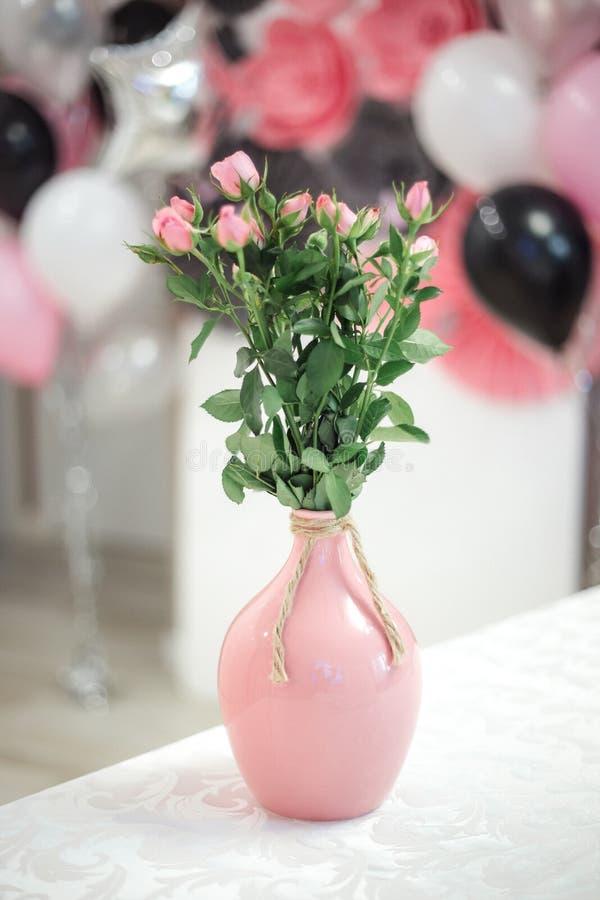在花瓶的甜桃红色玫瑰花在与后边气球的米黄被绘的木背景 库存照片