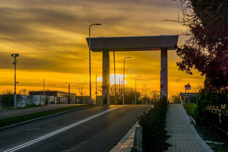 在莱茵河畔阿尔芬下,荷兰,与五颜六色的天空的日落Rijnhavenbrug的路  免版税库存图片