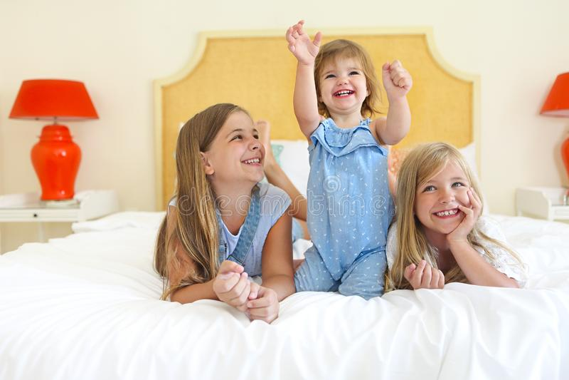 在获得的床上的三个妹乐趣 免版税库存图片