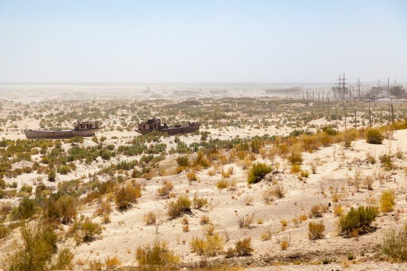 在船坟园的土气小船在Moynaq、穆伊纳克或者Moynoq -咸海或Aral湖附近的一片沙漠的-乌兹别克斯坦在中亚 免版税图库摄影