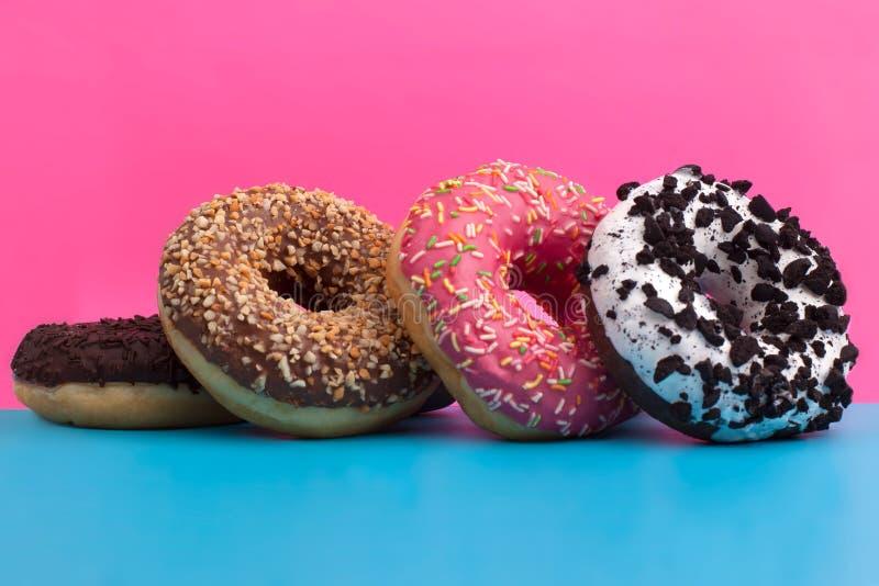 在蓝色和桃红色背景的四个不同油炸圈饼 免版税图库摄影