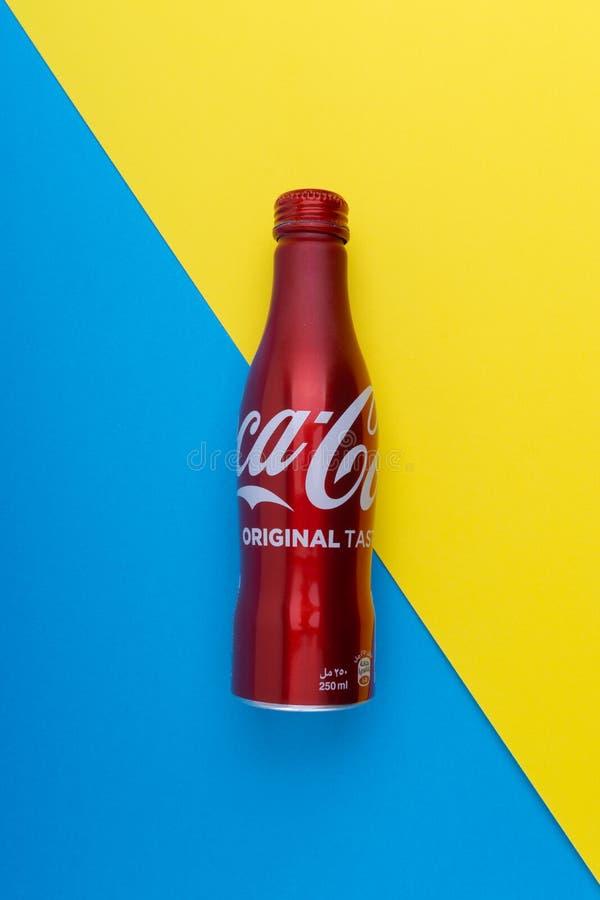 在蓝色和黄色背景的可乐或焦炭饮料 库存图片