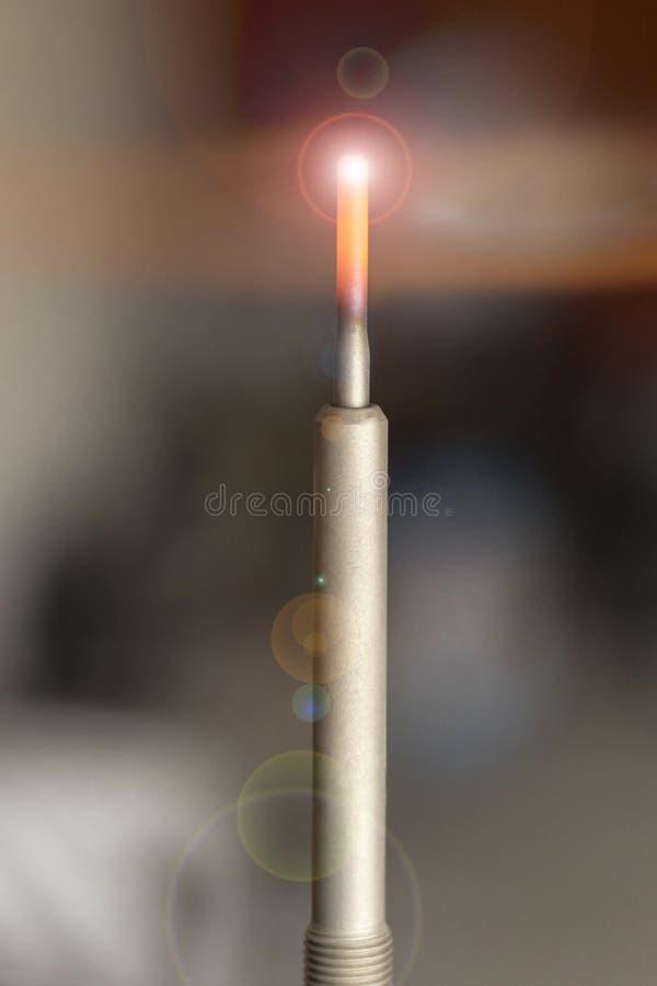 在蓝色手套的大师检查蜡烛 在汽车的机舱 特写镜头 库存照片