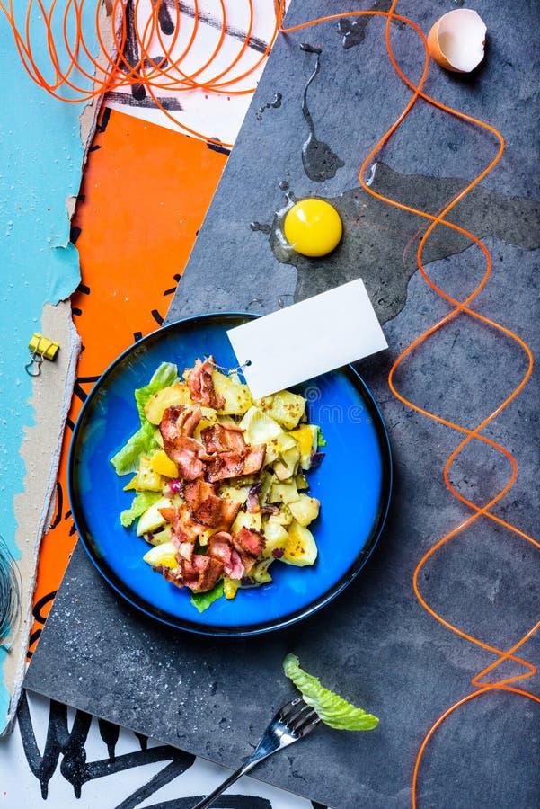 在蓝色碗的新鲜的酥脆烟肉、鲕梨和蛋沙拉 顶视图 库存照片
