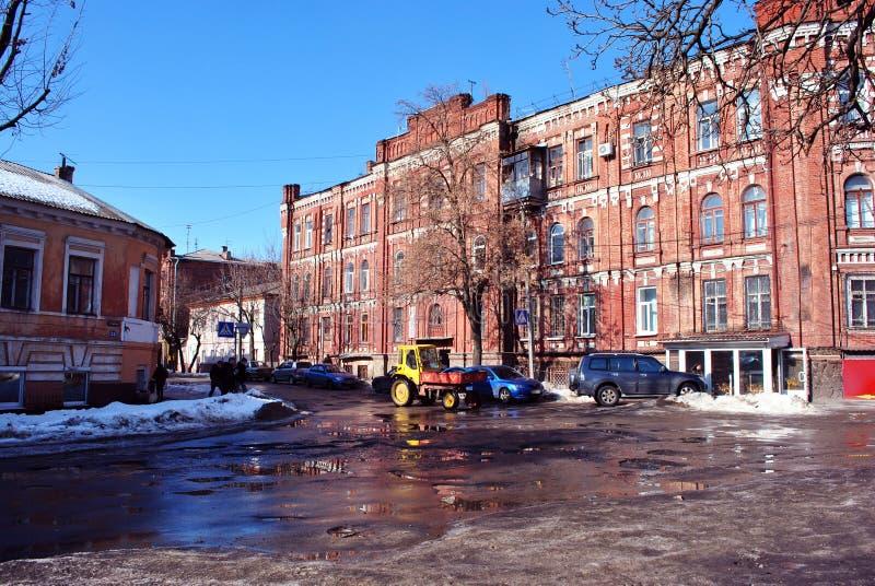 在老城市街道的明亮的黄色拖拉机,沿低故事公寓的路,冬天在乌克兰,哈尔科夫 库存照片