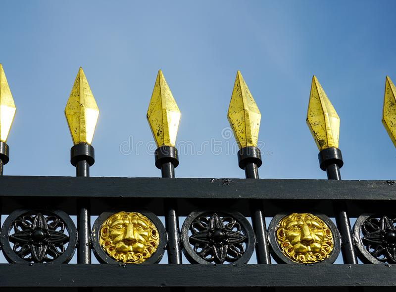在老wrought-iron篱芭的镀金的峰顶 免版税库存照片