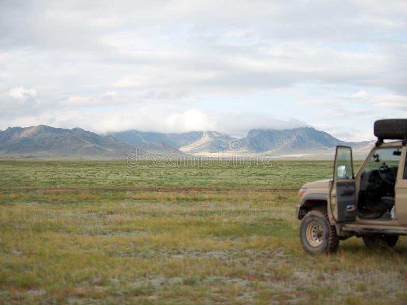 在蒙古干草原的SUV 向前与峰顶的山脉在云彩 免版税库存照片
