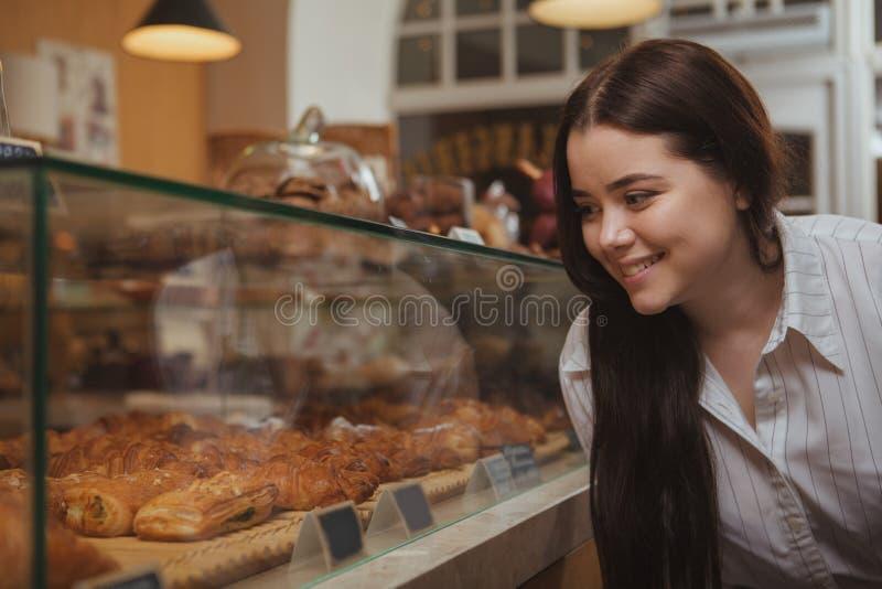 在面包店商店的有吸引力的年轻女人购物 库存照片