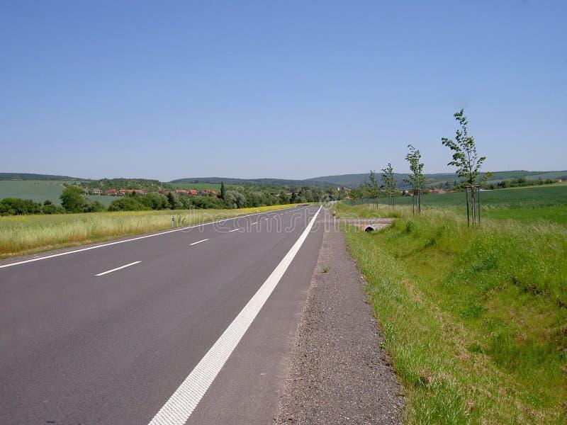 在领域与交叉路和线之间的新的柏油路 免版税库存照片