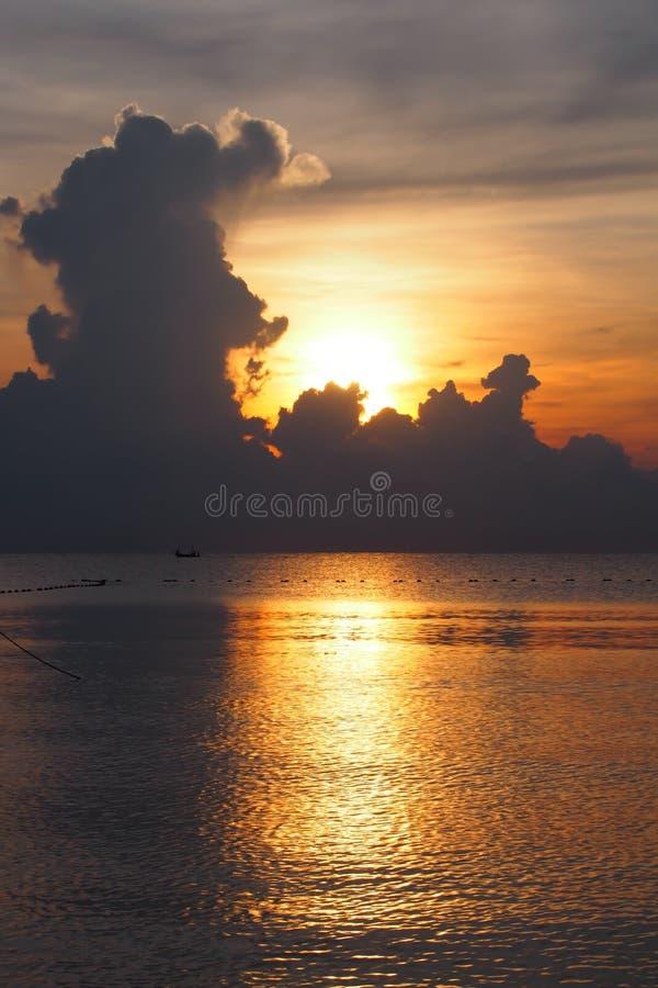 在风平浪静的渔船有日出的 免版税库存照片