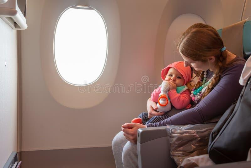 在飞行期间,母亲怀有她的婴儿婴儿 一起坐在飞机的窗口附近 图库摄影