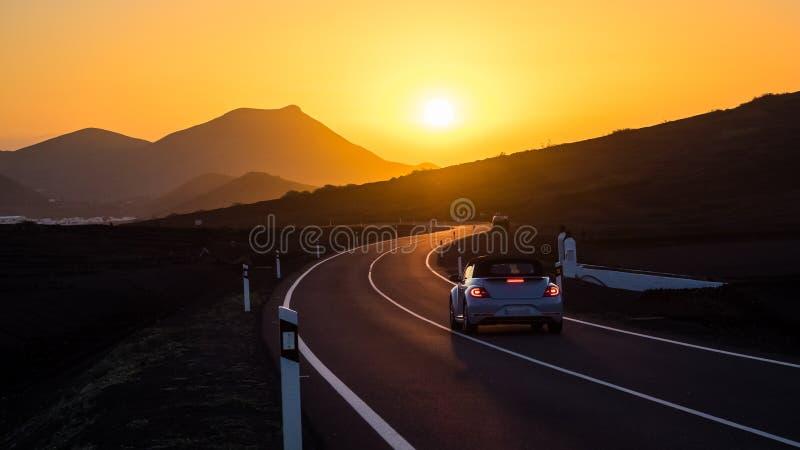在驾驶往日落的一个弯曲道路的汽车 免版税库存图片