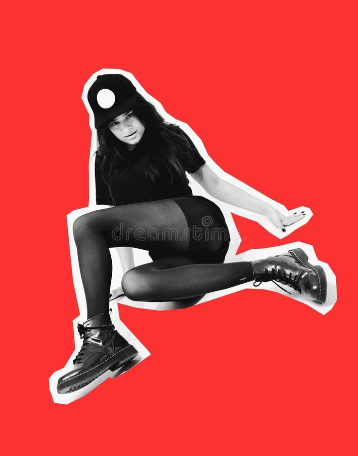 在黑上面、短裤、贴身衬衣和盖帽姿势打扮的时髦的年轻深色头发的女孩坐在白色的地板 库存照片