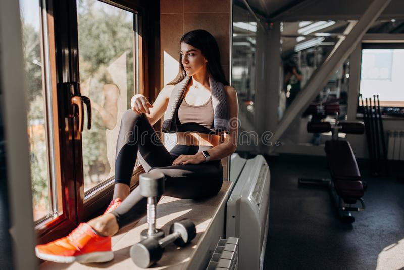 在黑体育上面和贴身衬衣打扮的美丽的运动女孩坐与哑铃的窗台在她旁边 免版税库存照片