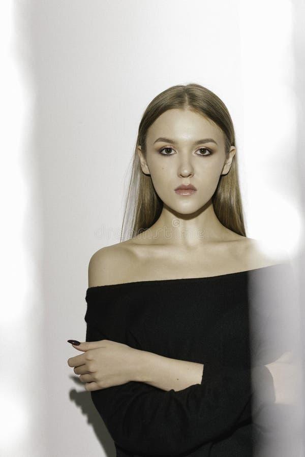 在黑毛线衣的美好的白肤金发的模型在与强光的白色背景 库存照片