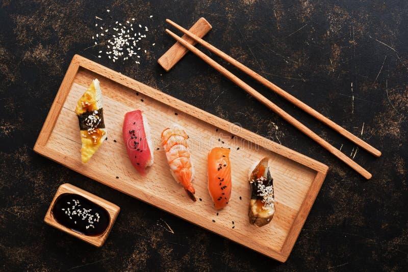 在黑暗的土气背景的被分类的寿司集合 在一块木板材的日本料理寿司,酱油,筷子 顶视图 免版税库存照片