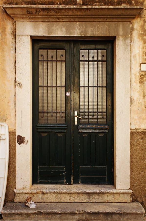 在黑暗的混凝土墙,空的抽象内部,方形的背景纹理的老棕色木门 免版税库存图片