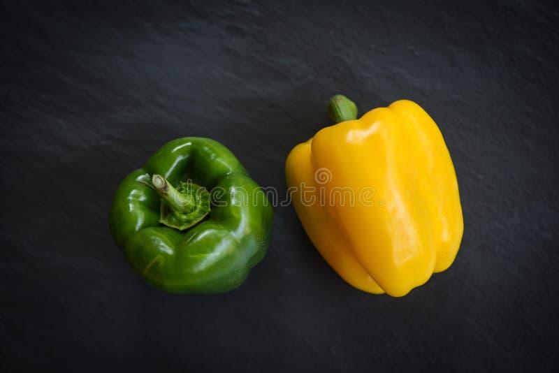 在黑暗的背景的新鲜的黄色和绿色甜椒胡椒 库存照片