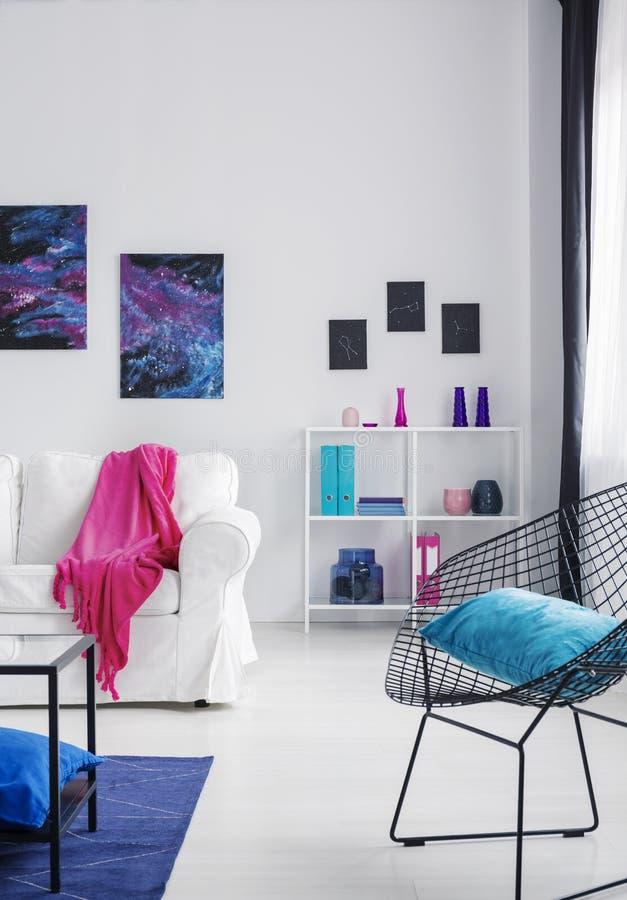 在黑时髦的金属扶手椅子的蓝色枕头在明亮的波斯菊启发了内部与白色家具,与拷贝空间的真正的照片  图库摄影