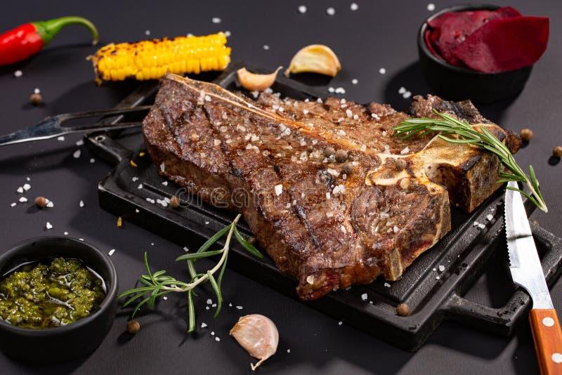 在黑石切板的可口牛排 烤肉服务与knif,烤玉米,大蒜,迷迭香,调味汁,辣椒 库存图片
