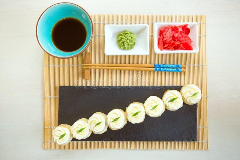 在黑背景隔绝的新嘎吱咬嚼的炸虾寿司卷 免版税库存照片