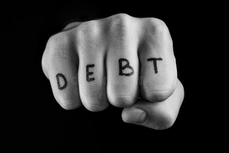 在黑背景,题字债务的拳头 免版税库存图片