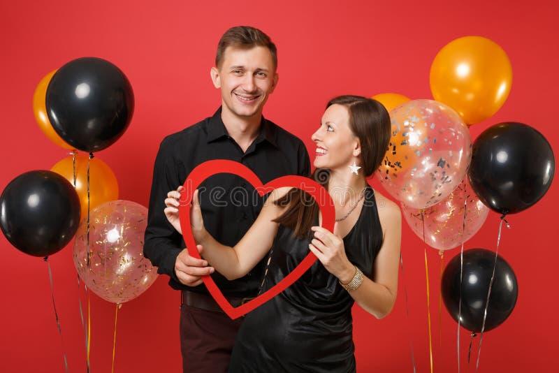 在黑色衣服的爱的夫妇拿着庆祝生日在明亮的红色背景空气的心脏节日晚会 库存图片