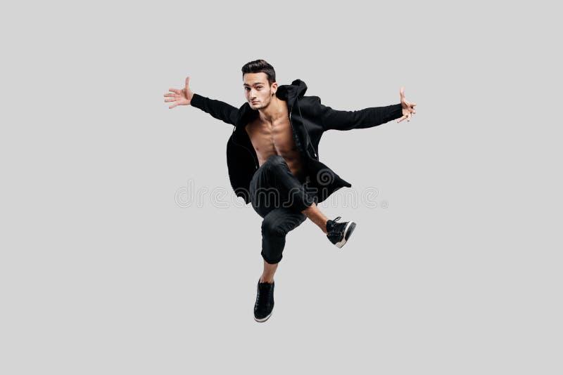 在黑色裤子和一件运动衫打扮的街道跳舞的英俊的舞蹈家在赤裸躯干跳并且涂他的胳膊 免版税库存照片