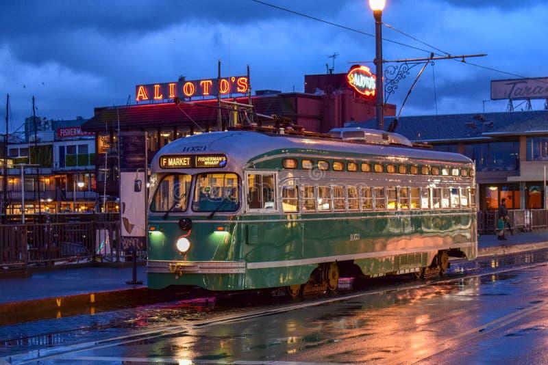 在黄昏的旧金山五颜六色的湿街道与电车,路面电车 免版税库存照片