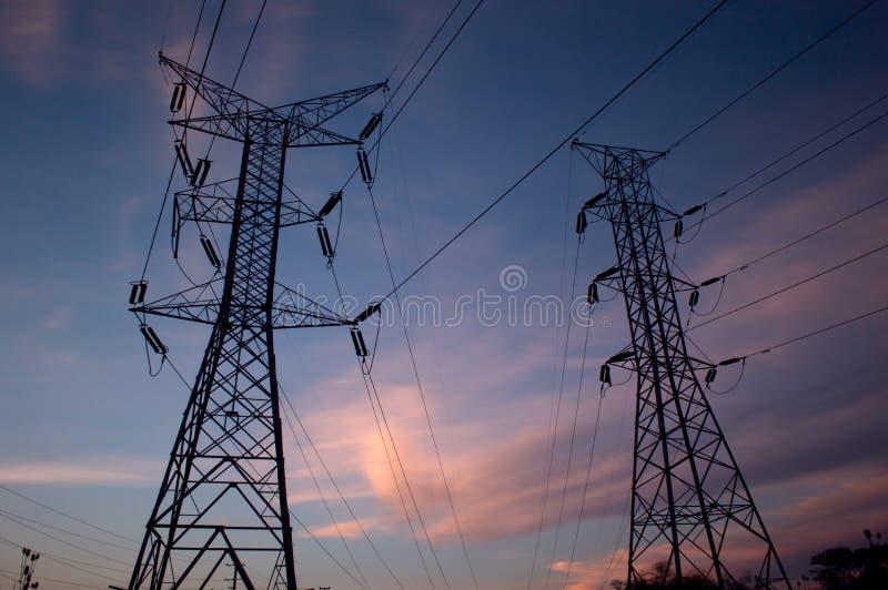 在黄昏的现出轮廓的输电线 免版税库存照片