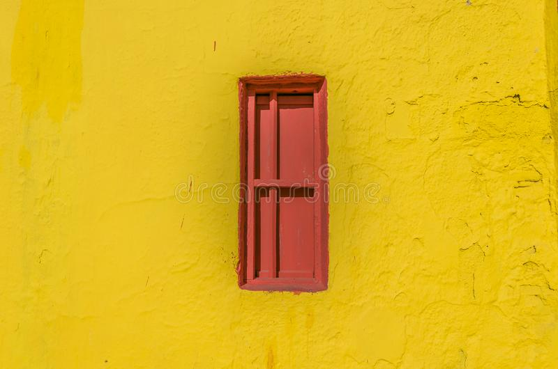 在黄色墙壁的红色闭合的禁止的窗口 免版税图库摄影