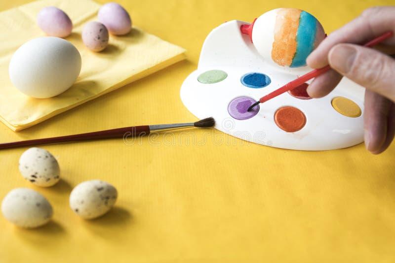 在黄色桌上的绘的复活节彩蛋 免版税图库摄影