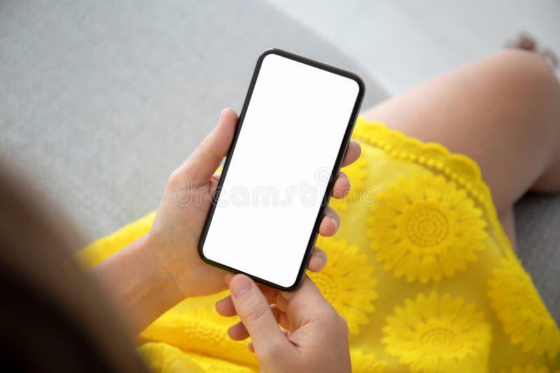 在黄色礼服藏品电话的女性手有屏幕的 图库摄影