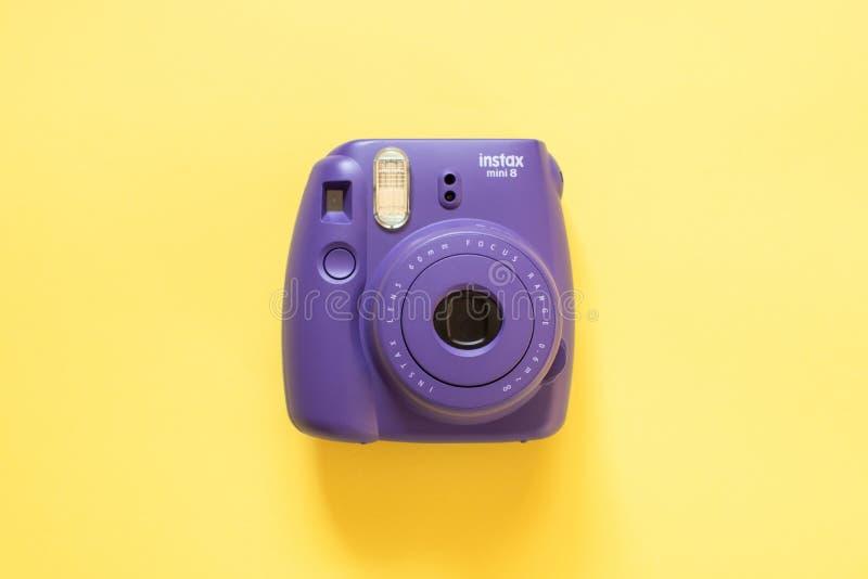 在黄色背景的富士胶片instax微型照相机 免版税库存照片