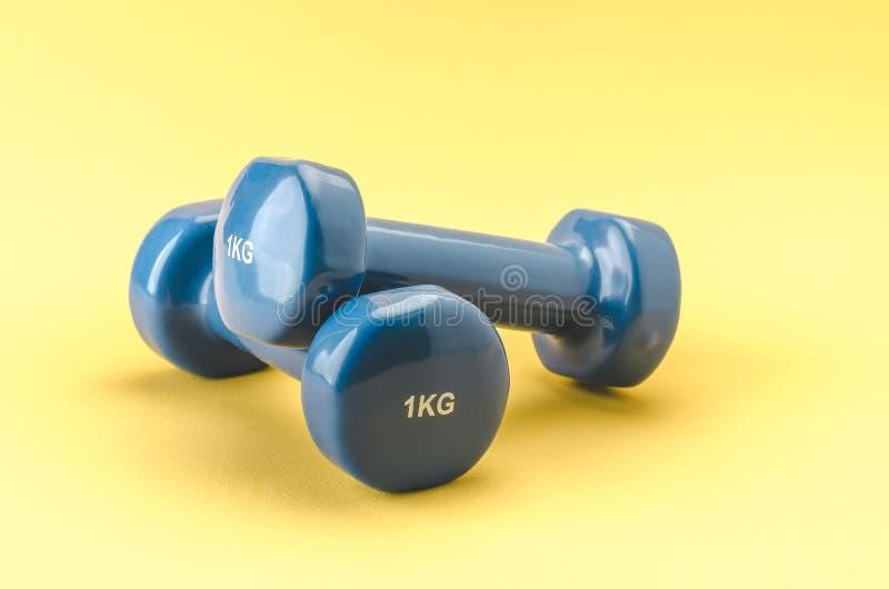 在黄色背景/acessories的两个蓝色光滑的哑铃健身类的 库存图片
