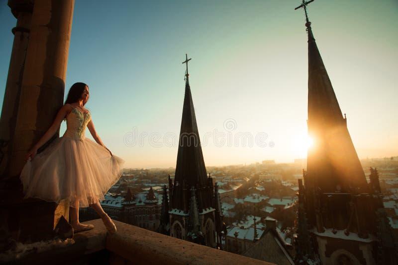 在阳台的美好的芭蕾舞女演员舞蹈在日落的都市风景背景的 免版税图库摄影