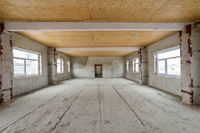 在重建下的未完成的公寓或房子大顶楼室 胶合板天花板,涂灰泥的墙壁,窗口开头,水泥地板 库存图片