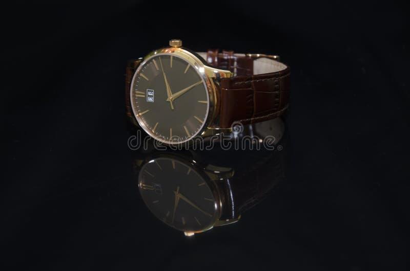 在金子的手表在黑背景 库存图片