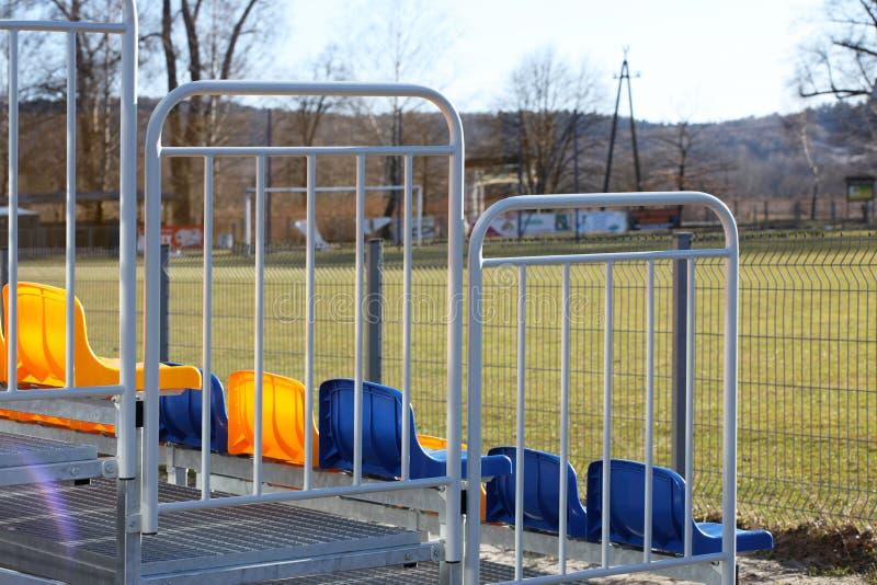 在金属轻的建筑的橄榄球场的新的立场有塑料位子的在蓝色和黄色 球迷的地方在体育场内 库存照片