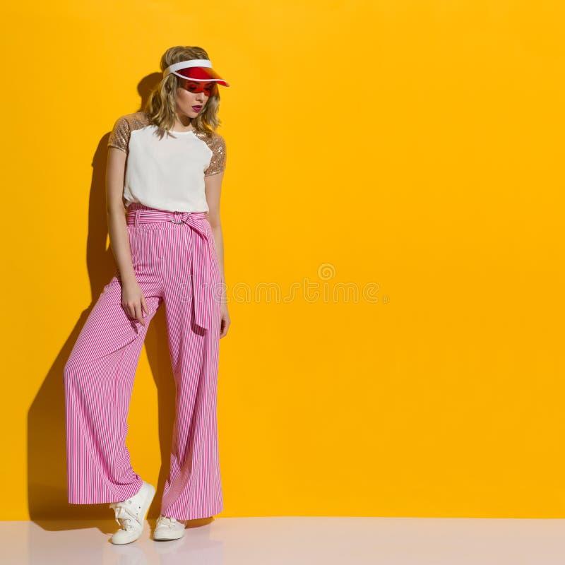 在镶边宽腿长裤和透明遮阳帘的时装模特儿在阳光下站立 免版税库存图片