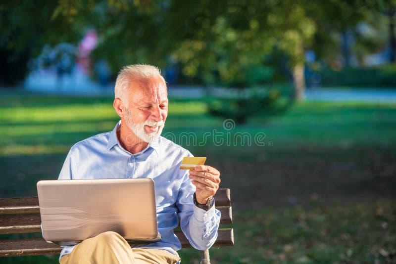 在长凳和冲浪的网在膝上型计算机在公园,购物的网上概念的老男性开会 免版税图库摄影