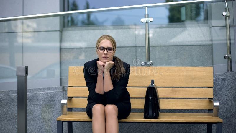 在长凳的哀伤的女性开会,遭受消沉,运作,不用乐趣 免版税库存照片