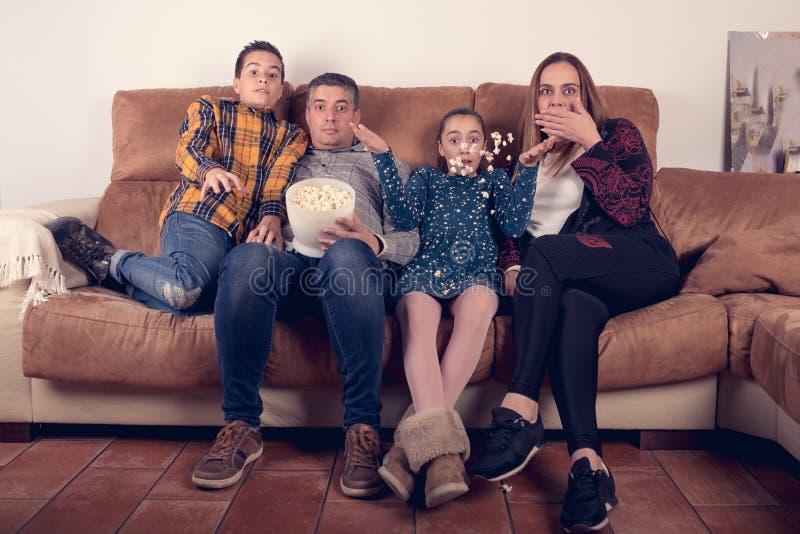 在长沙发的家庭观看的恐怖电影在家和吃玉米花 免版税库存图片
