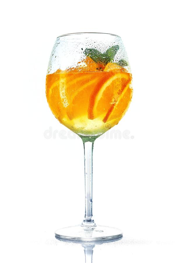 在酒杯的橙色鸡尾酒用在白色背景的薄菏 Misted玻璃 免版税库存照片