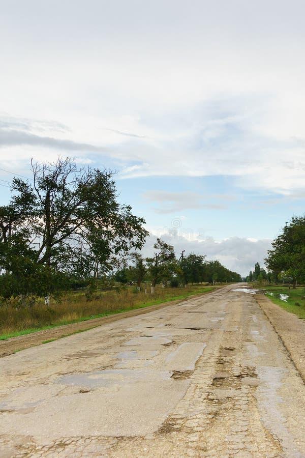 在雨以后弄湿老被毁坏的路在克里米亚 免版税库存照片