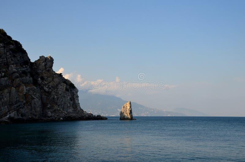 在雅尔塔和阿尤岛Dag山的背景的风帆岩石在黑海 免版税库存图片