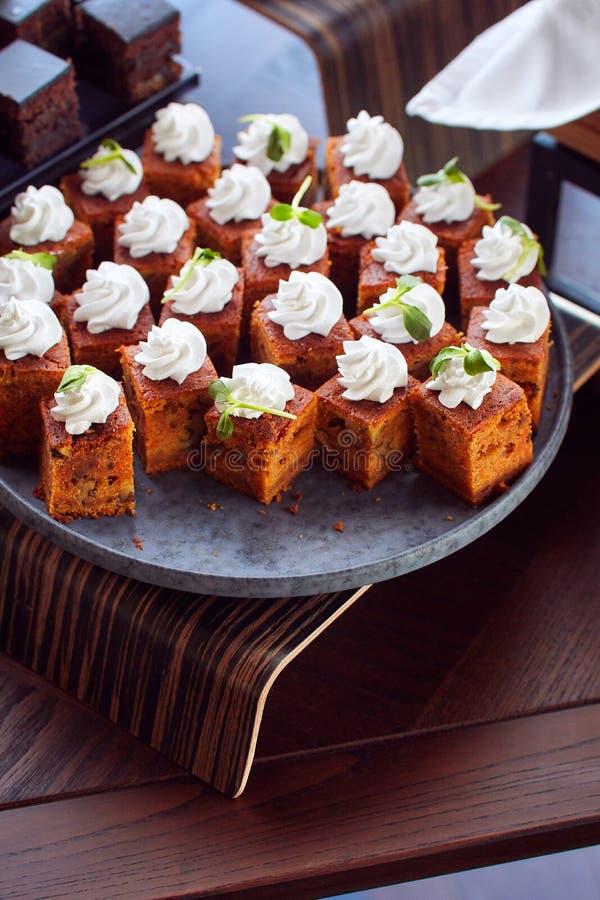 在陶瓷板材与奶油色顶部和绿色的服务少量蛋糕 免版税库存图片